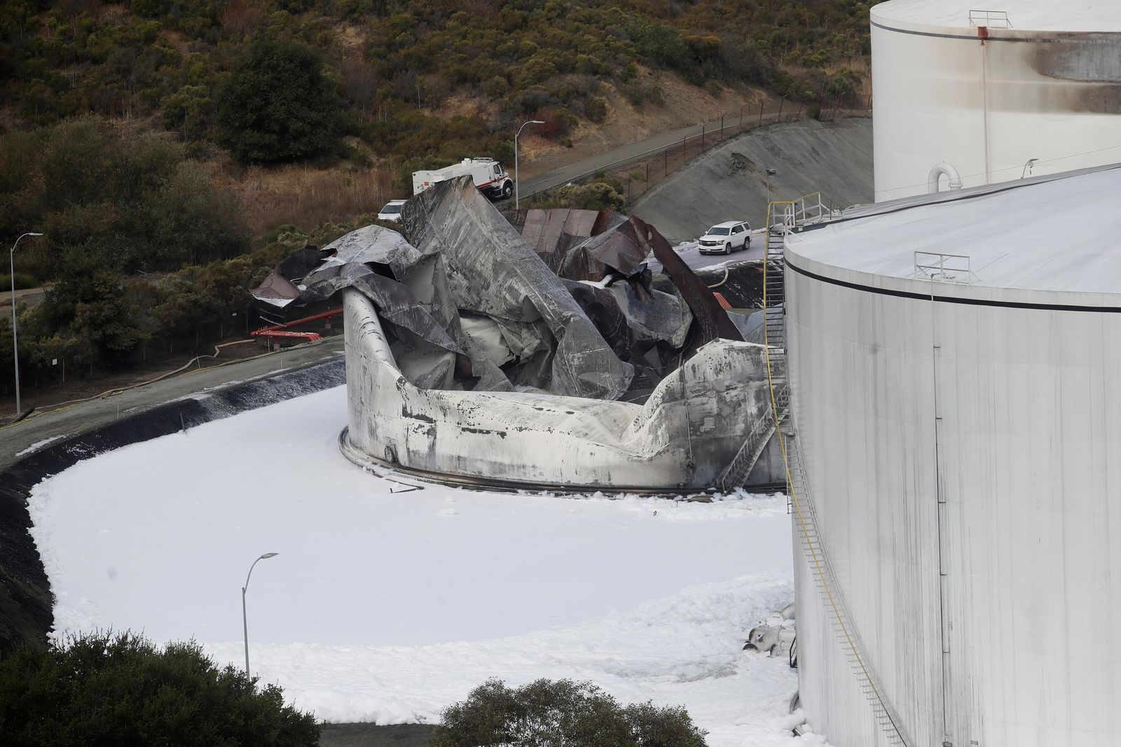 Damage from a Tuesday, Oct. 15, 2019, fire is shown at NuStar Energy fuel storage facility in Crockett, Calif., Wednesday, Oct. 16, 2019. Officials were trying to determine Wednesday if a 4.5 magnitude earthquake triggered an explosion at the fuel storage facility in the San Francisco Bay Area that started a fire and trapped thousands in their homes for hours because of potentially unhealthy air. (AP Photo/Jeff Chiu)