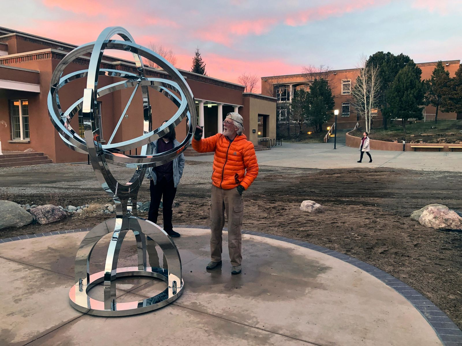 In this Dec. 11, 2019 photo Bill Donahue, center, a retired teacher and director of laboratories at St. John's College, uses an armillary sphere to track planetary rotations and explore the history of astronomy in Santa Fe, N.M. The unique precision-steel replica of an instrument created by Danish astonomer Tycho Brahe was commissioned by graduates of the college where students trace the evolution of math and science from early civilizations. (AP Photo/Morgan Lee)