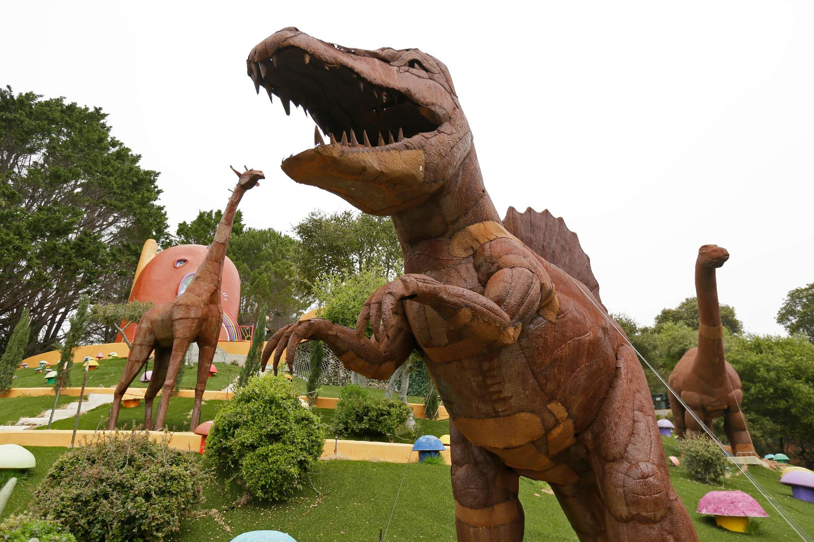 In this photo taken Monday, April 1, 2019, dinosaurs and other figurines stand in the backyard of the Flintstone House in Hillsborough, Calif. The San Francisco Bay Area suburb of Hillsborough is suing the owner of the house, saying that she installed dangerous steps, dinosaurs and other Flintstone-era figurines without necessary permits. The owner and her attorney say they will fight for the rights of property owners and Fred and Barney fans everywhere. (AP Photo/Eric Risberg)