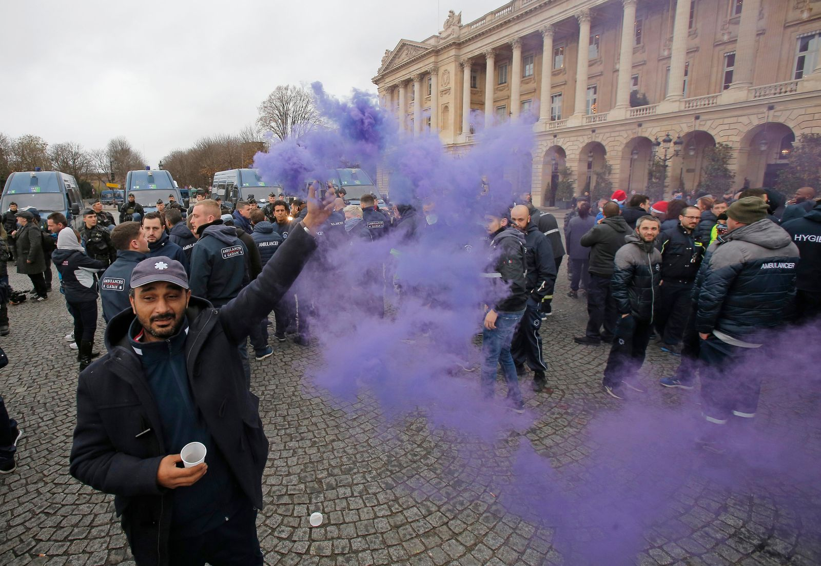 An ambulance worker holds a flare as he and his fellows block the Place de la Concorde in Paris, Monday, Dec. 3, 2018. Ambulance workers took to the streets and gathered close to the National Assembly in downtown Paris to complain about changes to working conditions as French Prime Minister Edouard Philippe is holding crisis talks with representatives of major political parties in the wake of violent anti-government protests that have rocked Paris. (AP Photo/Michel Euler)