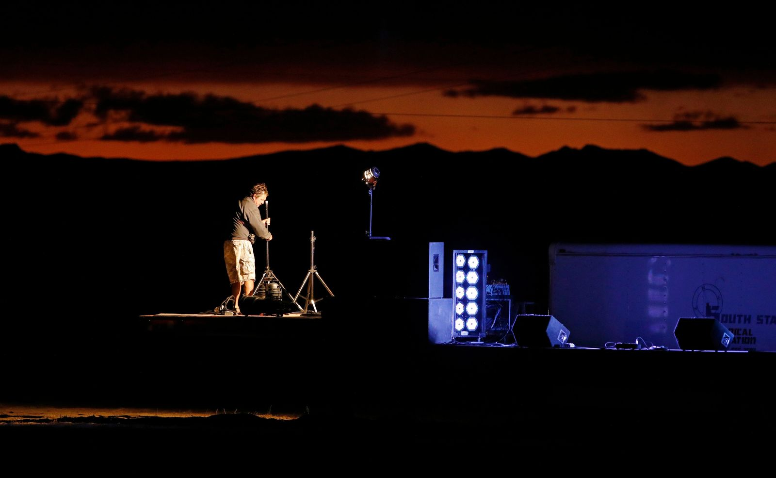 "A man sets up a stage in preparation for an event inspired by the ""Storm Area 51"" internet hoax near the Little A'Le'Inn motel and cafe, Thursday, Sept. 19, 2019, in Rachel, Nev. Hundreds have arrived in the desert after a Facebook post inviting people to ""see them aliens"" got widespread attention and gave rise to festivals this week. (AP Photo/John Locher)"