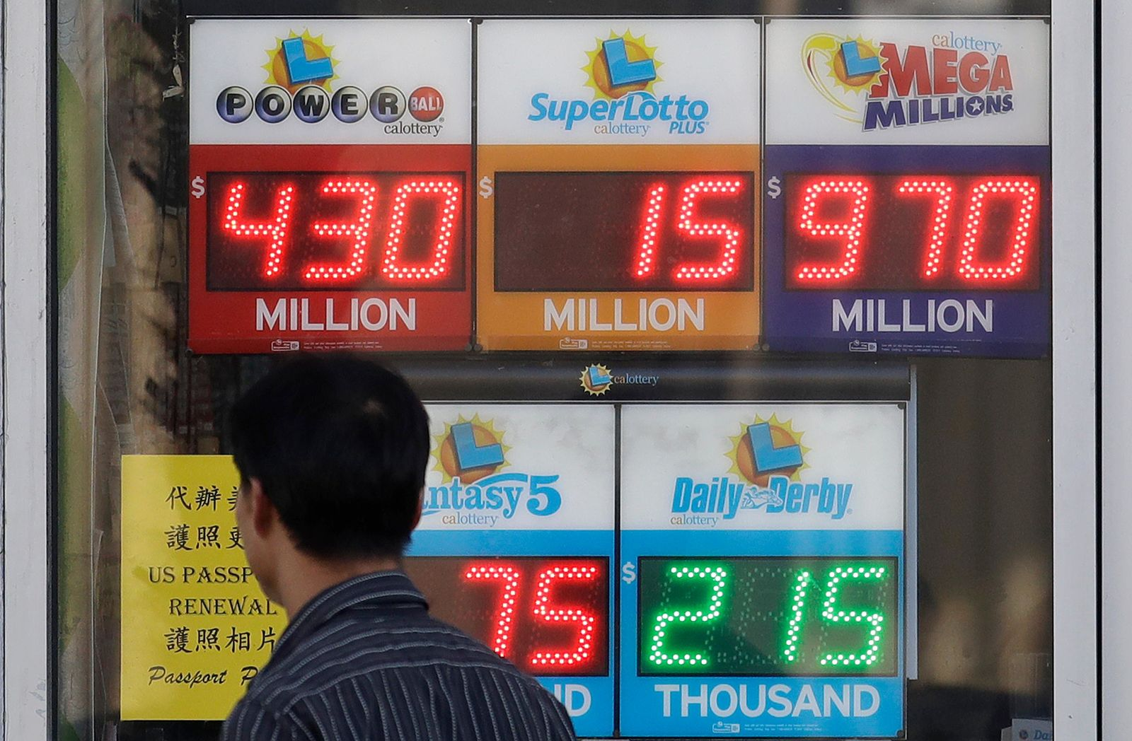 A man walks past Mega Millions and other lottery displays outside of The Lucky Spot in San Francisco, Thursday, Oct. 18, 2018. The Mega Millions jackpot has climbed to $970 million, inching ever-closer to the $1 billion mark. (AP Photo/Jeff Chiu)