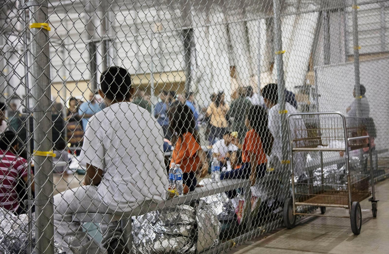 FILE - In this June 17, 2018, file photo, provided by U.S. Customs and Border Protection, people who have been taken into custody related to cases of illegal entry into the United States, sit in one of the cages at a facility in McAllen, Texas. Advocates were shocked to find an underage mom and her tiny, premature newborn daughter huddled in a Border Patrol facility this week in what they say was another example of the poor treatment immigrant families receive after crossing the border. The mother is a Guatemalan teen who crossed the border without a parent and was held at a facility in McAllen, Texas. (U.S. Customs and Border Protection's Rio Grande Valley Sector via AP, File)
