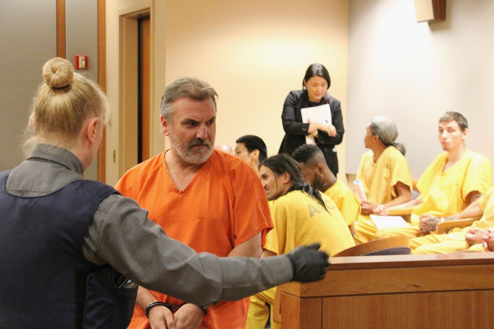 Brian Steven Smith, second from left, is escorted out of a courtroom in Anchorage, Alaska, Monday, Oct. 21, 2019. Smith has pleaded not guilty to 14 charges stemming from the deaths of two Alaska Native women. (AP Photo/Mark Thiessen)