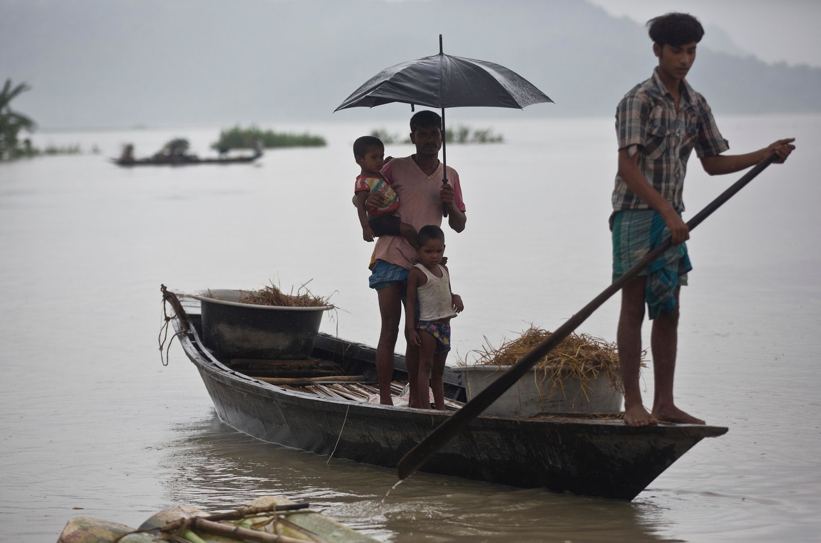 Flood affected villagers travel on a boat in Katahguri village along the river Brahmaputra, east of Gauhati, India, Sunday, July 14, 2019. Officials in northeastern India said more than a dozen people were killed and over a million affected by flooding. Rain-triggered floods, mudslides and lightning have left a trail of destruction in other parts of South Asia. (AP Photo/Anupam Nath)
