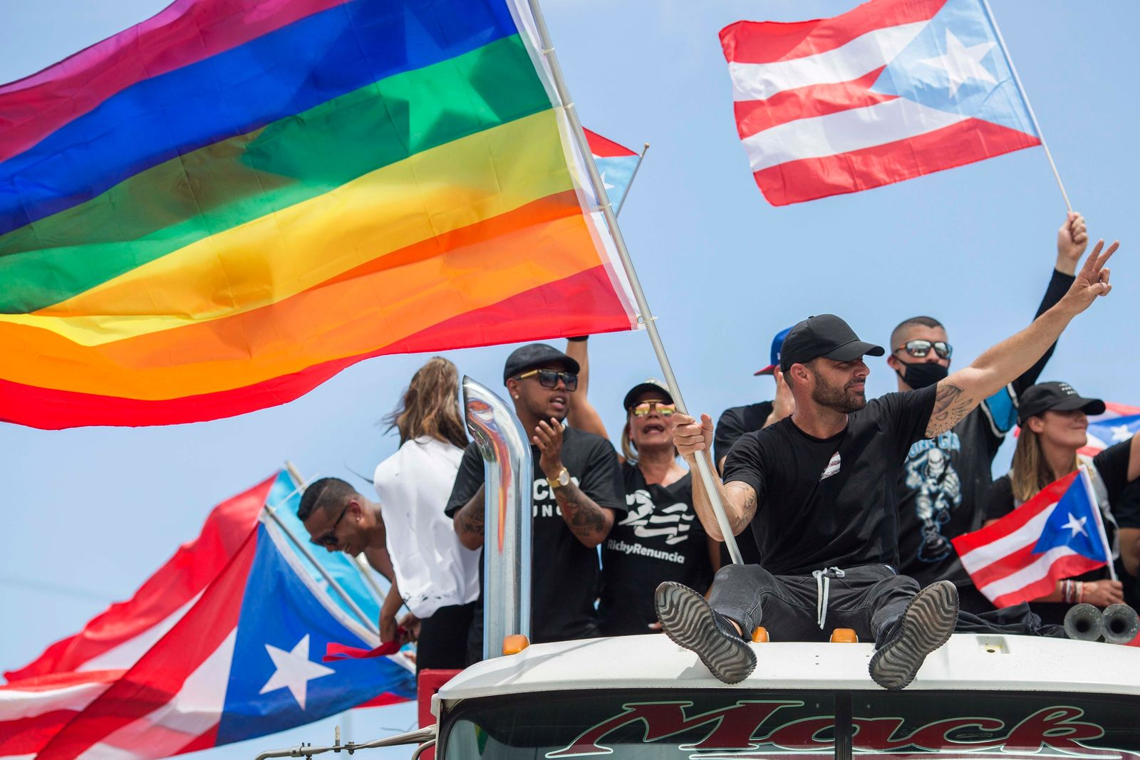 Ricky Martin, flying a gay pride flag, joins a protest to demand the resignation of Governor Ricardo Rossello from office, in San Juan, Puerto Rico, Monday, July 22, 2019. (AP Photo/Dennis M. Rivera Pichardo)
