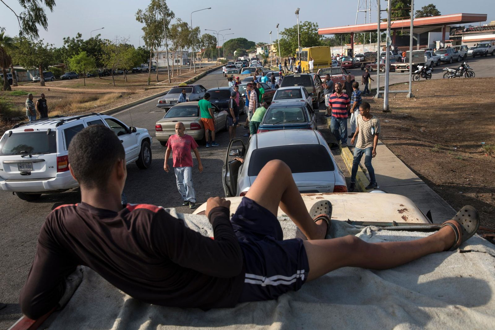 People line the street with their vehicles as they wait to fill up with gas at a fuel station, top right, in Cabimas, Venezuela, Wednesday, May 15, 2019. . (AP Photo/Rodrigo Abd)