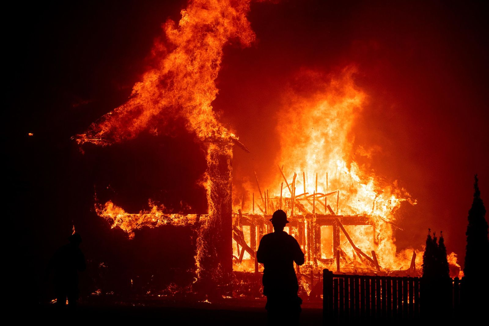 FILE - In this Nov. 8, 2018, file photo, a home burns during a wildfire in Paradise, Calif. Paradise High School, in the Northern California town that was mostly destroyed by a wildfire in November 2018, is scheduled to play its first football game Friday, Aug. 23, 2019. (AP Photo/Noah Berger, File)