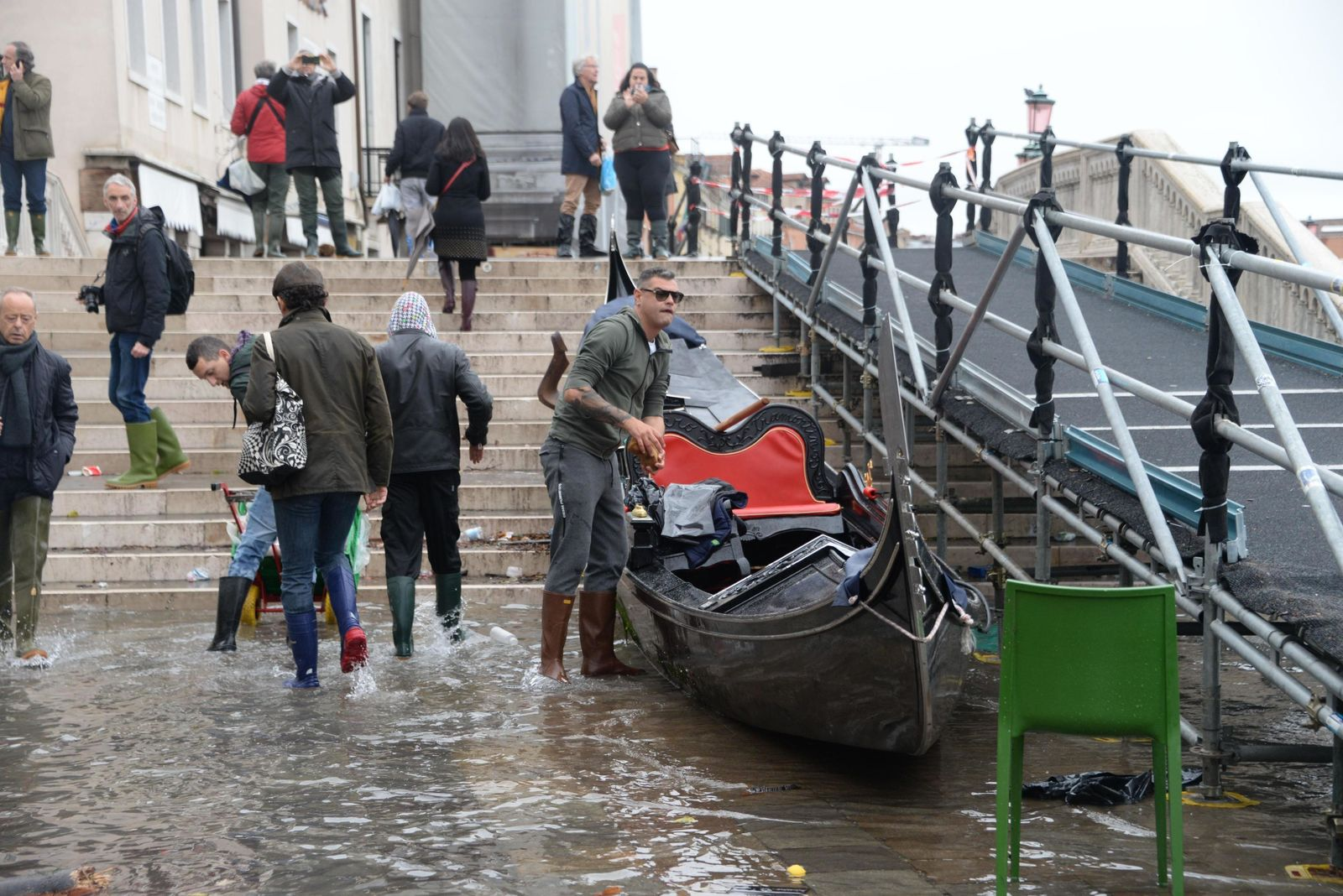 A man clean up a gondola boat after a high tide, in Venice, Italy, Wednesday, Nov. 13, 2019.{ } (Andrea Merola/ANSA via AP)