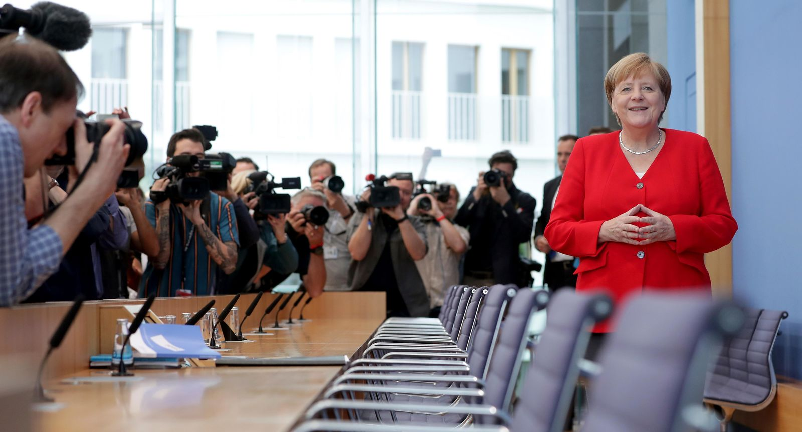 German Chancellor Angela Merkel, right, smiles as she arrives for her annual sommer press conference in Berlin, Germany, Friday, July 19, 2019. (AP Photo/Michael Sohn)