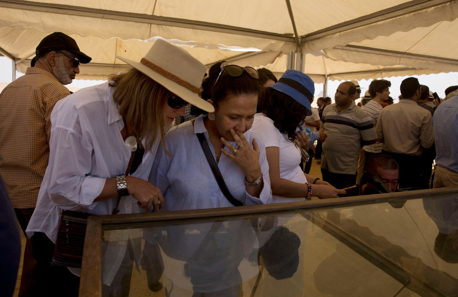 Women look at recently discovered artifacts at the Bent Pyramid during an event opening the pyramid and its satellites for visitors in Dashur, Egypt, Saturday, July 13, 2019. (AP Photo/Maya Alleruzzo)