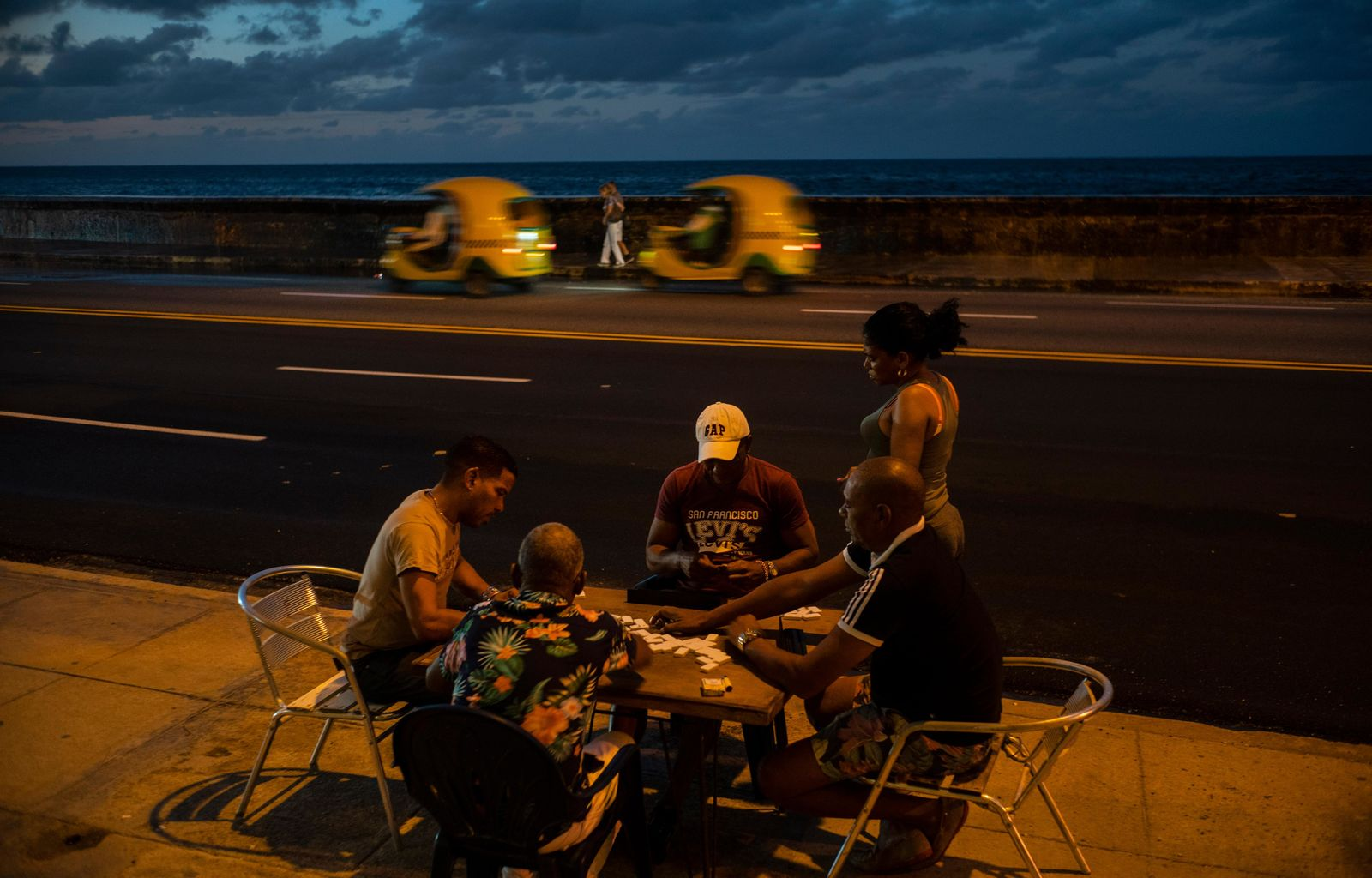 In this Nov. 10, 2019 photo, people play dominoes near the malecon sea wall at sunset in Havana, Cuba. The city will celebrate its 500th anniversary on Nov. 16. (AP Photo/Ramon Espinosa)