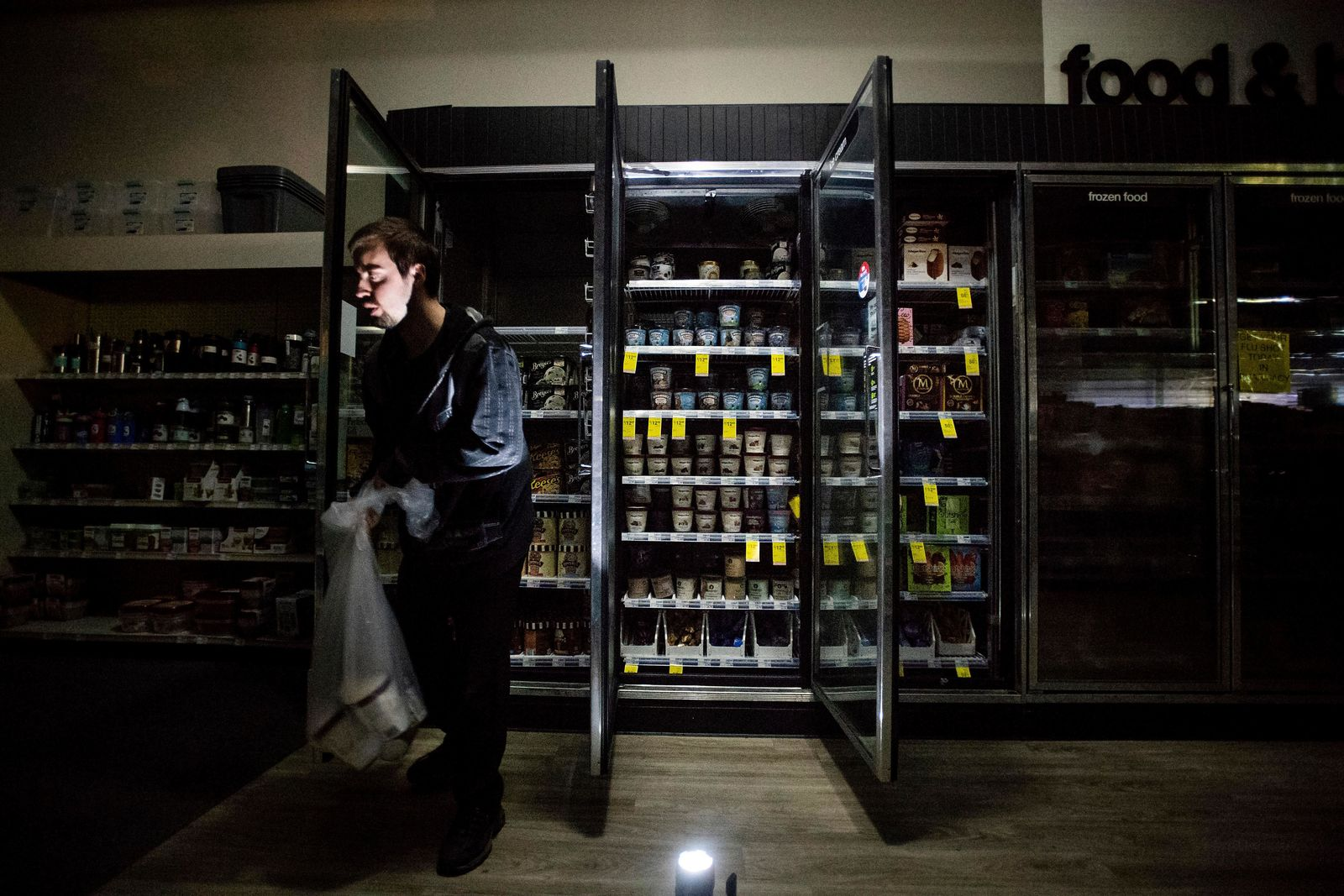 FILE - In this Oct. 9, 2019, file photo, CVS Pharmacy shift supervisor James Quinn throws out ice cream from darkened freezers as downtown Sonoma, Calif., remains without power.{ } { }(AP Photo/Noah Berger, File)