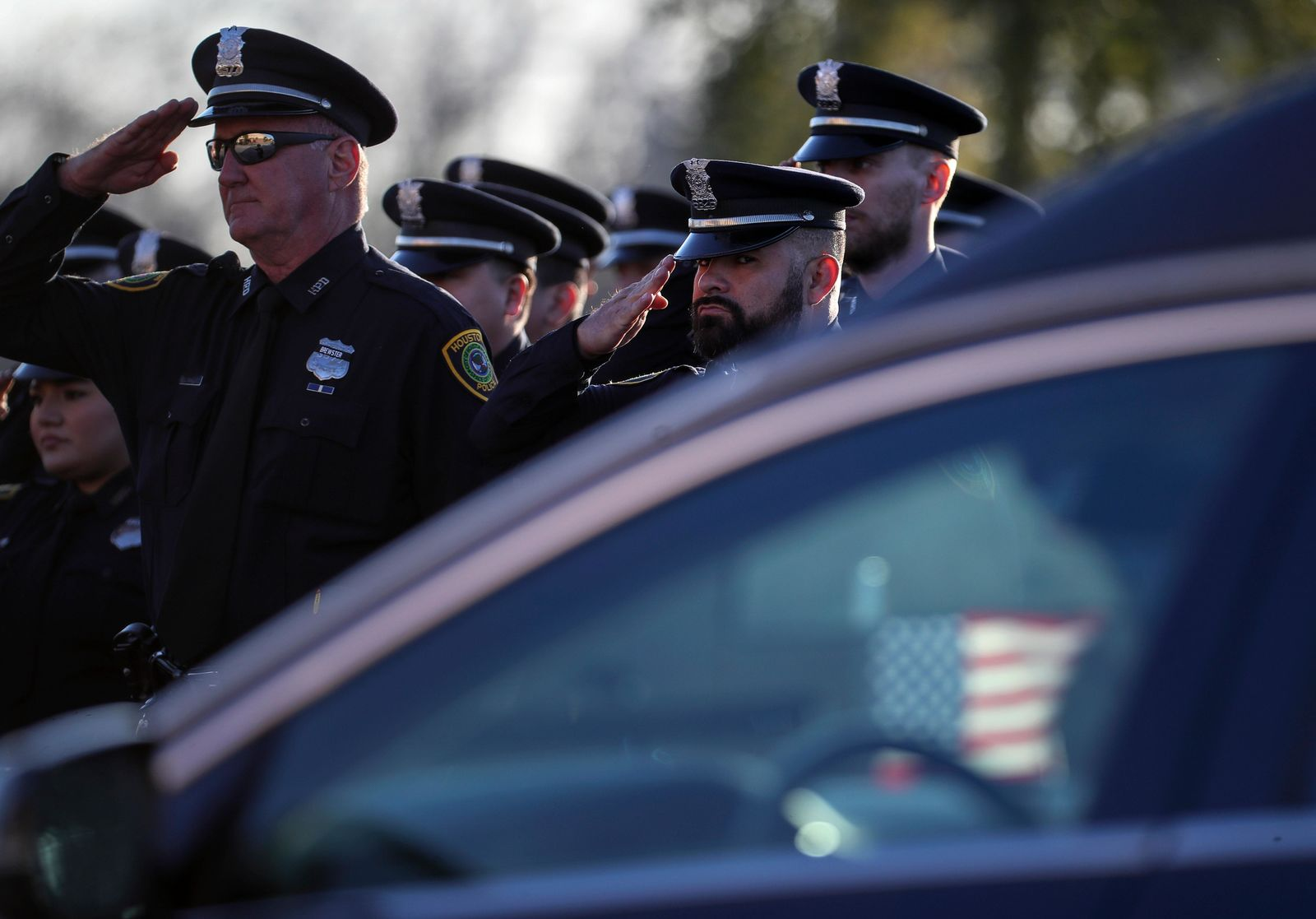 Members of Houston Police Eastside Patrol Division salute as the casket carrying Houston police Sgt. Christopher Brewster arrives, Thursday, Dec. 12, 2019, at Grace Church Houston in Houston. Brewster, 32, was gunned down Saturday evening, Dec. 7, while responding to a domestic violence call in Magnolia Park. Police arrested 25-year-old Arturo Solis that night in the shooting death. Solis faces capital murder charges. (Jon Shapley/Houston Chronicle via AP)