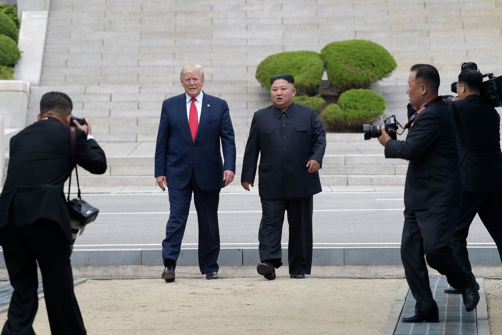 FILE - In this June 30, 2019, file photo, President Donald Trump, center left, and North Korean leader Kim Jong Un walk on the North Korean side at the border village of Panmunjom in the Demilitarized Zone. (AP Photo/Susan Walsh, File)
