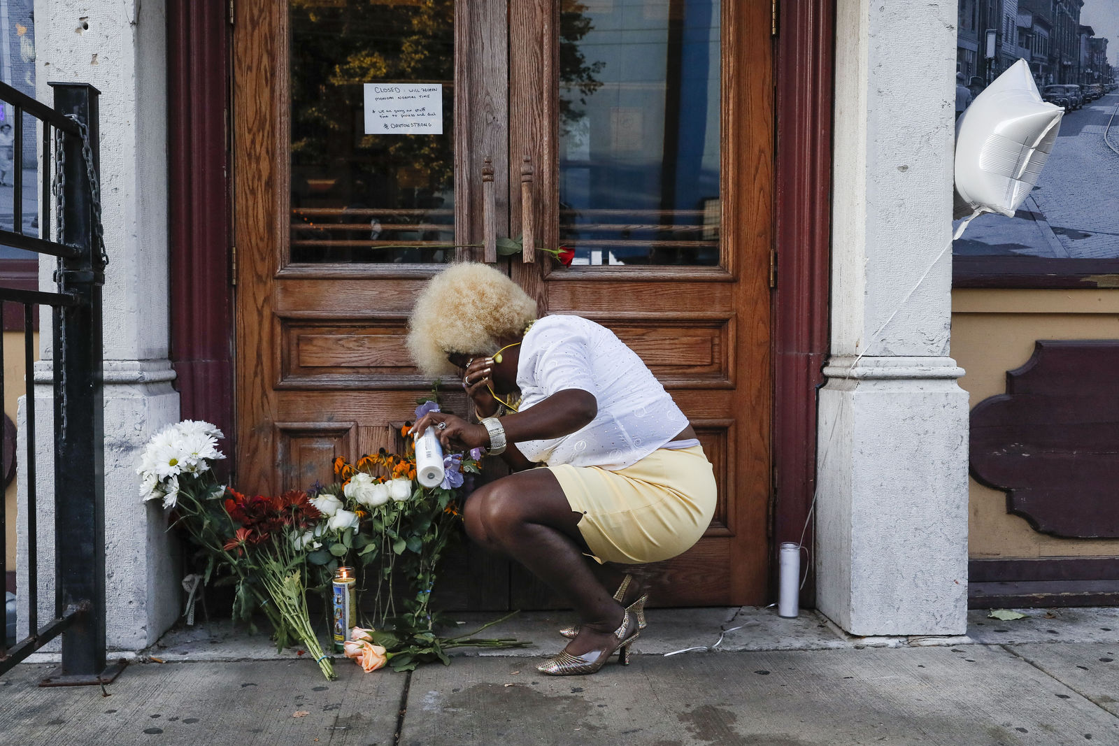 Mourners place flowers and candles at the front of Ned Peppers bar while they gather at the scene of a mass shooting before a prayer vigil, Sunday, Aug. 4, 2019, in Dayton, Ohio. Multiple people in Ohio have been killed in the second mass shooting in the U.S. in less than 24 hours, and the suspected shooter is also deceased, police said. (AP Photo/John Minchillo)