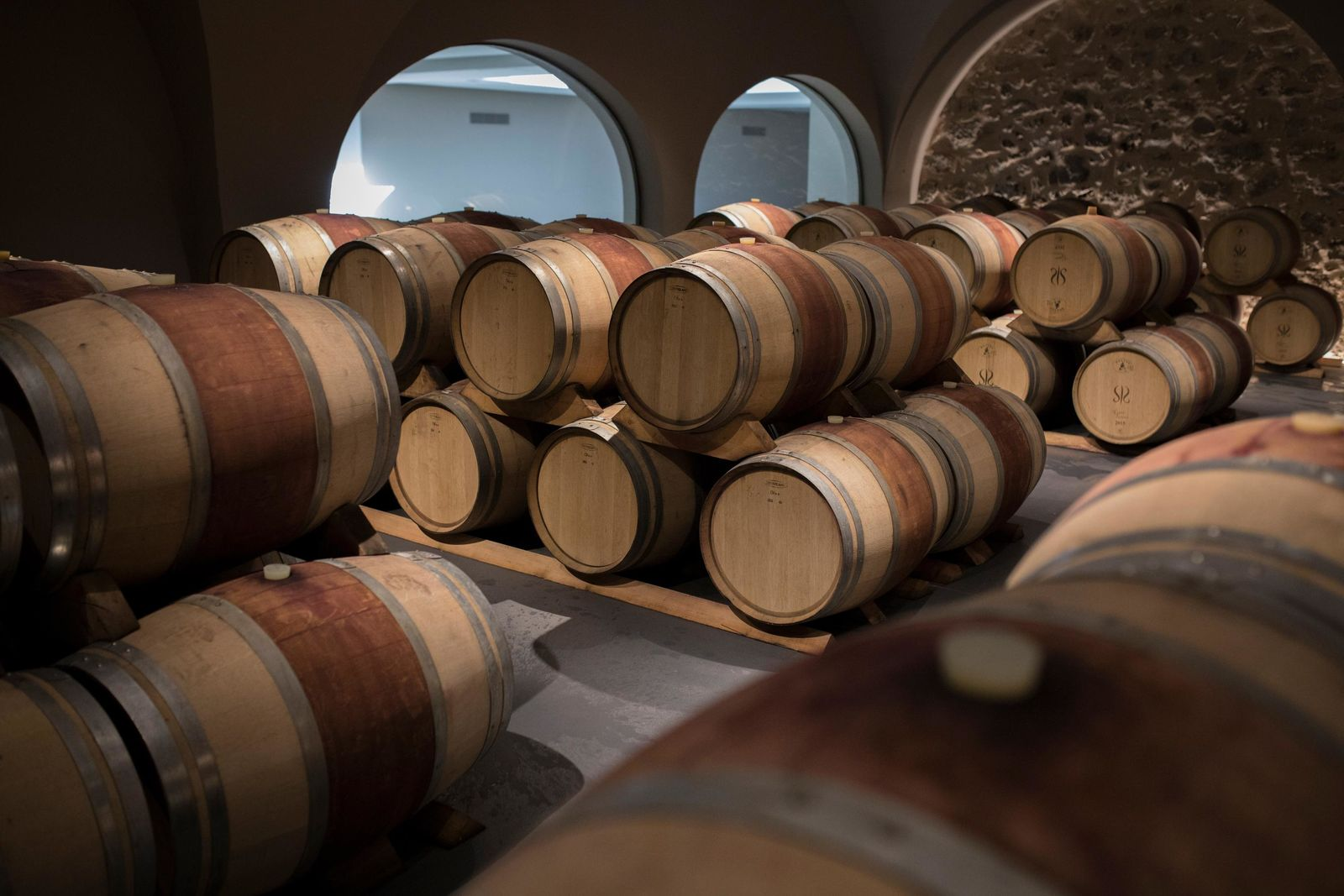 Wine barrels sit in a wine cellar in the southern France region of Provence, Friday Oct. 11, 2019. (AP Photo/Daniel Cole)