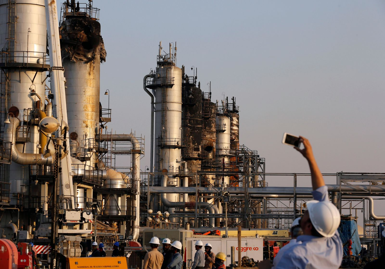 During a trip organized by Saudi information ministry, a cameraman films Aramco's oil processing facility after the recent Sept. 14 attack in Abqaiq, near Dammam in the Kingdom's Eastern Province, Friday, Sept. 20, 2019. (AP Photo/Amr Nabil)