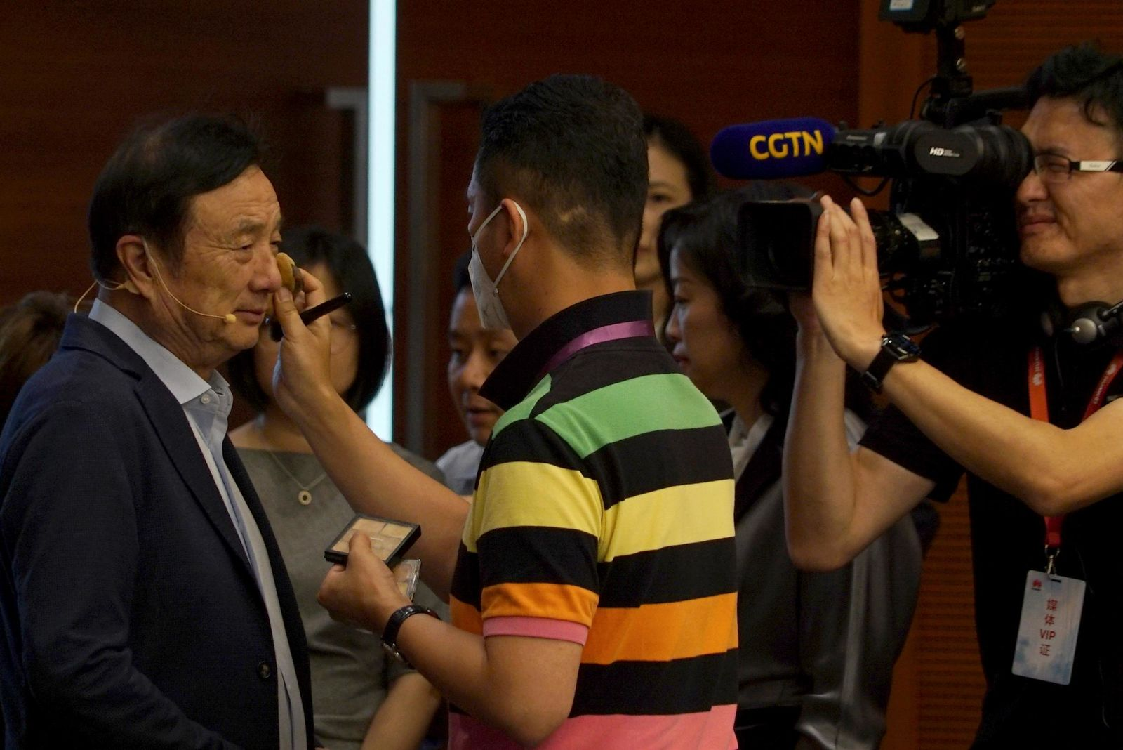 Huawei founder Ren Zhengfei, left, gets make up on his face before attending a roundtable at the telecom giant's headquarters in Shenzhen in southern China on Monday, June 17, 2019.{ } (AP Photo/Dake Kang)