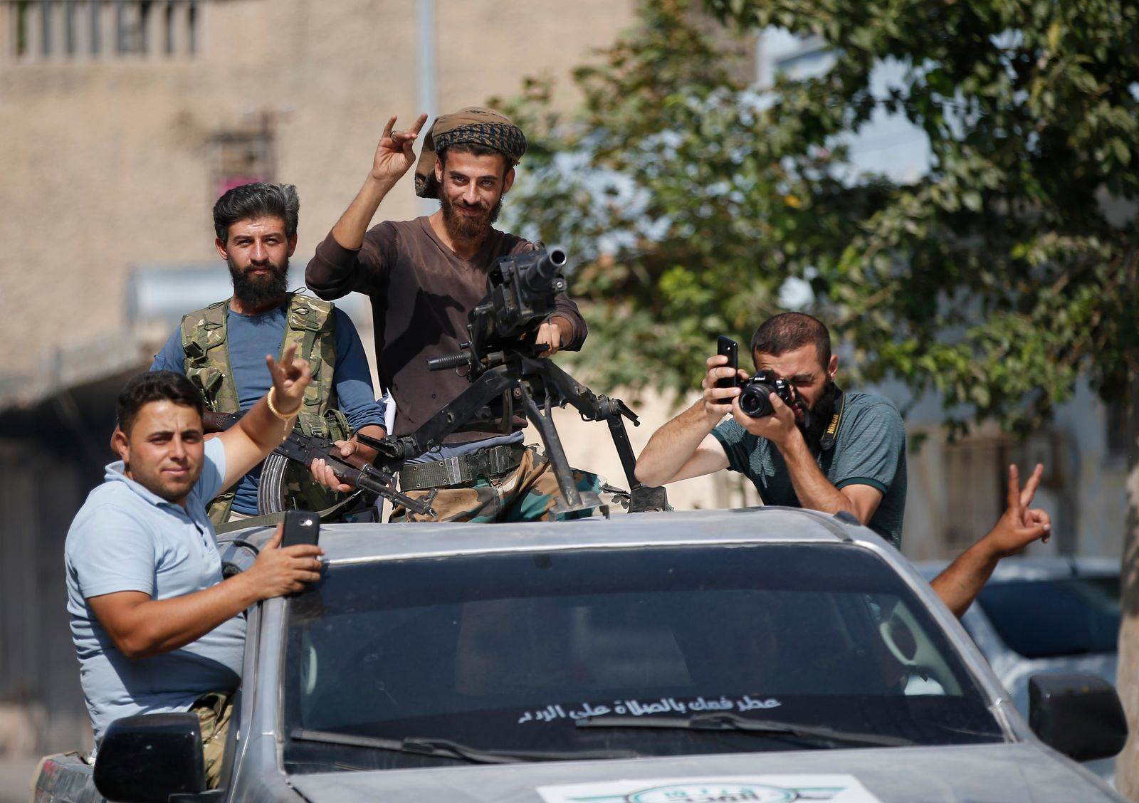 Turkish-backed Syrian opposition fighters cheer from a car as they drive around the border town of Akcakale, Sanliurfa province, southeastern Turkey, on their way to Tal Abyad, Syria, Monday, Oct. 14, 2019. (AP Photo/Lefteris Pitarakis)