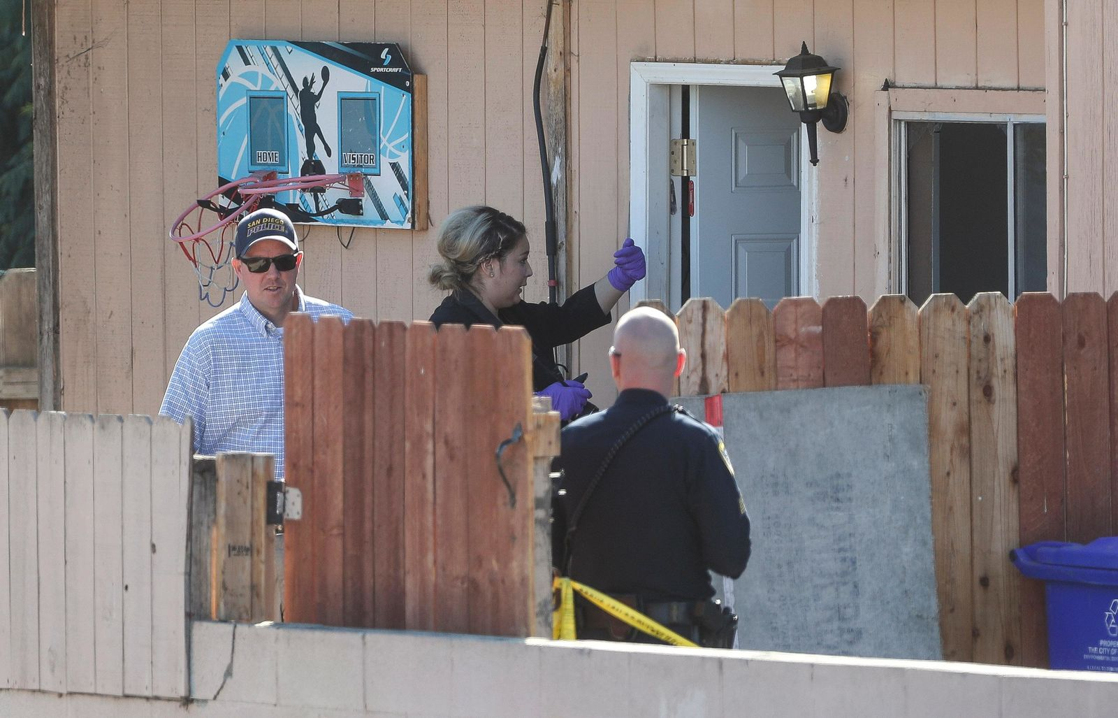San Diego Police investigate the home where two adults and three children died from gunshot wounds during a domestic shooting in the Paradise Hills area in San Diego, Calif., Saturday, Nov. 16, 2019. A husband and wife and three of their young children died Saturday morning at the family's San Diego home in what police believe was a murder-suicide sparked by a bitter divorce. One son is in critical condition. (Hayne Palmour IV/The San Diego Union-Tribune via AP)