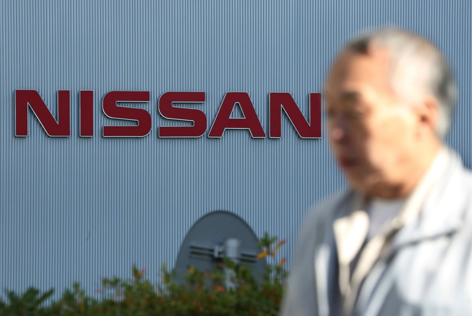 In this Jan. 9, 2019, photo, a man walks past the logo at global headquarters of Nissan Motor Co., Ltd. in Yokohama, near Tokyo.{ } (AP Photo/Koji Sasahara)