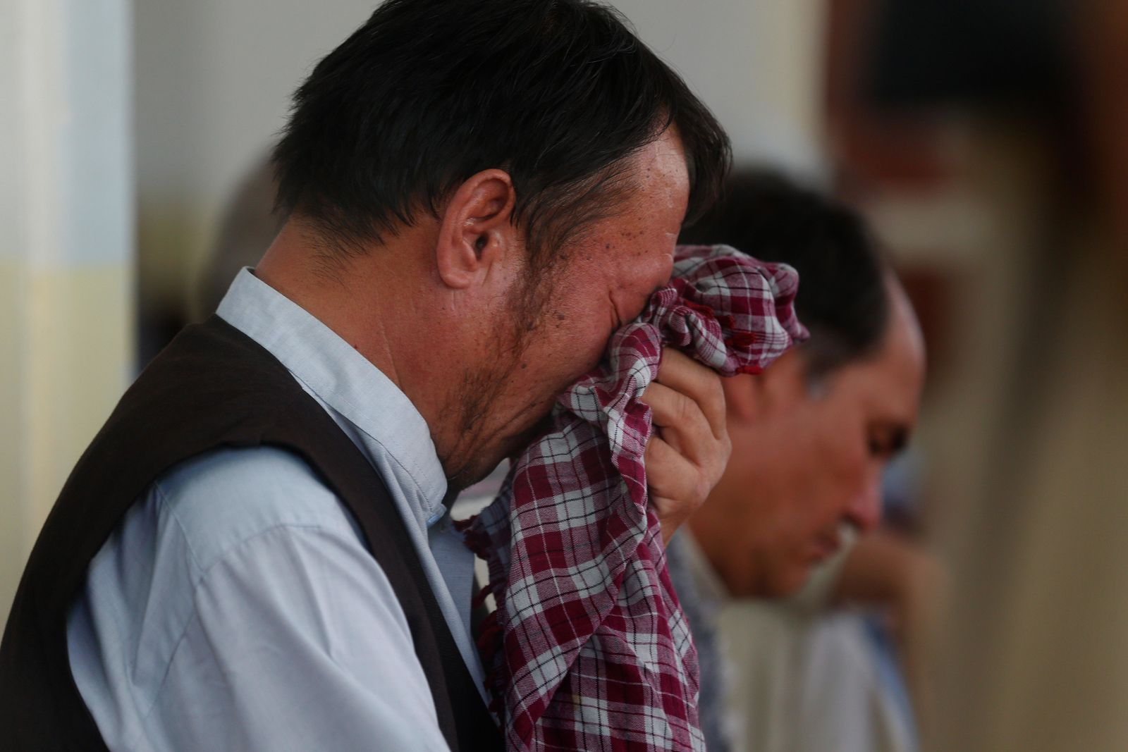 Men mourn for the victims of the Dubai City wedding hall bombing during a memorial service at a mosque in Kabul, Afghanistan, Tuesday, Aug. 20, 2019. (AP Photo/Rafiq Maqbool)