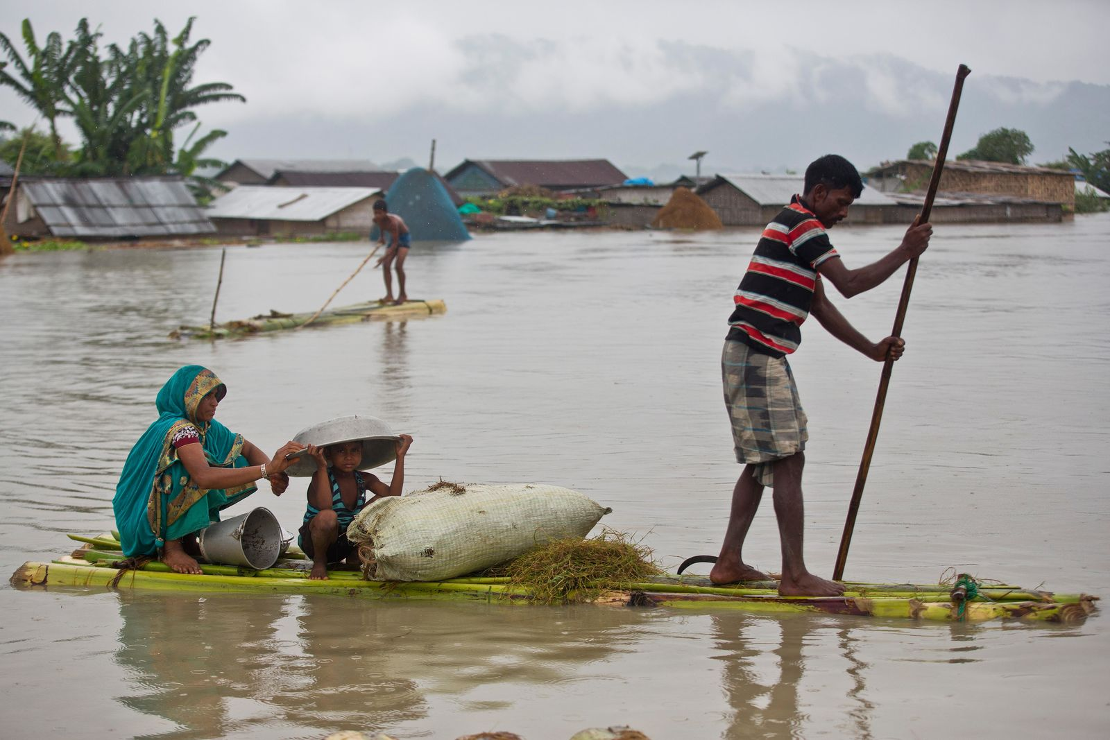 Flood affected villagers move on a makeshift bamboo raft in Katahguri village along the river Brahmaputra, east of Gauhati, India, Sunday, July 14, 2019. Officials in northeastern India said more than a dozen people were killed and over a million affected by flooding. Rain-triggered floods, mudslides and lightning have left a trail of destruction in other parts of South Asia. (AP Photo/Anupam Nath)