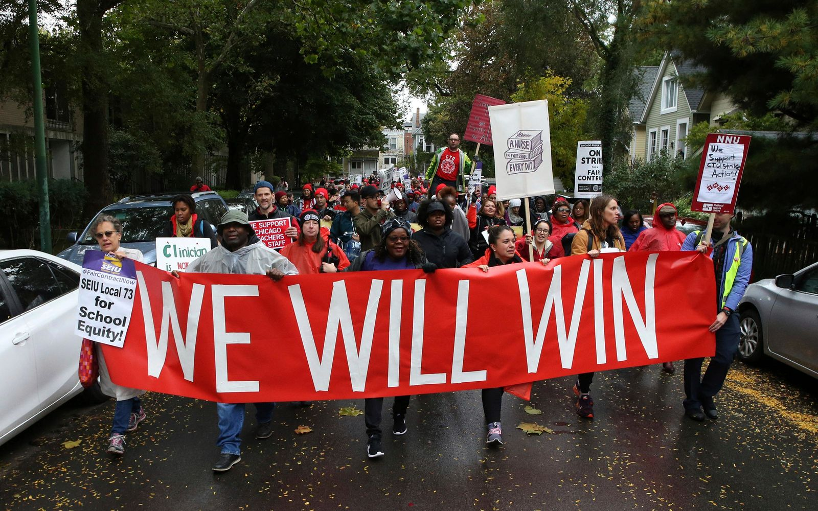 "Dozens of Chicago Teachers Union members and supporters march through the streets of Chicago's Hyde Park neighborhood during the ""Nurse in Every School"" Solidarity March for Justice on Monday, Oct. 21, 2019. (Antonio Perez/Chicago Tribune via AP)"