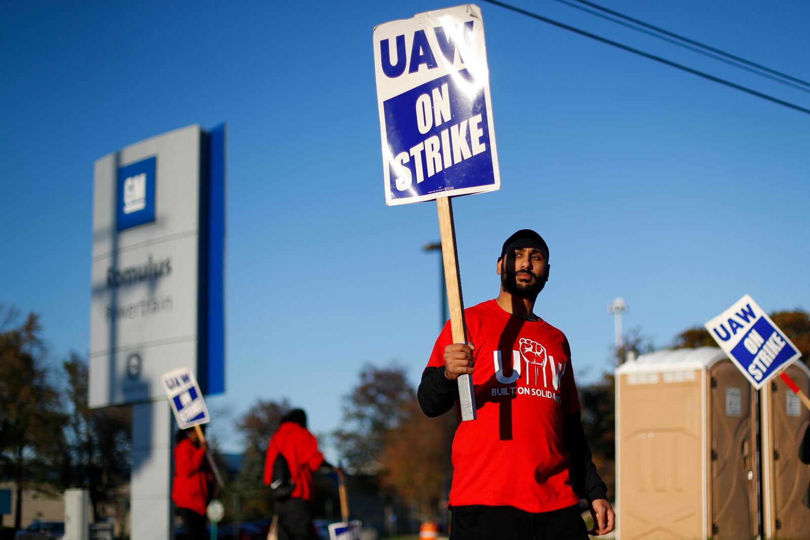 FILE - In this Oct. 9, 2019, file photo a member of the United Auto Workers walks the picket line at the General Motors Romulus Powertrain plant in Romulus, Mich.{ } (AP Photo/Paul Sancya, File)