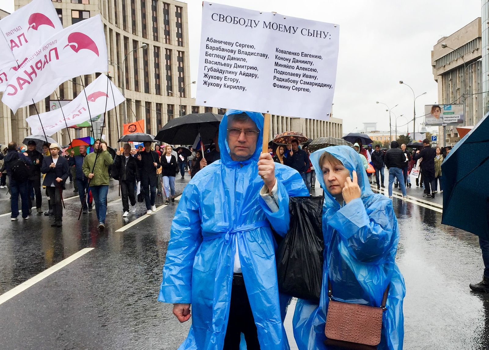 "In this photo taken on Aug. 10, 2019, Vyacheslav Abanichev and Alisa Abanicheva, parents of Sergei Abanichev charged with rioting connected to an opposition rally, hold a poster saying ""Free My Son"" with the names of all those arrested as they attend an opposition rally in Moscow, Russia.{ } (Daria Zelenaya/Novaya gazeta via AP)"