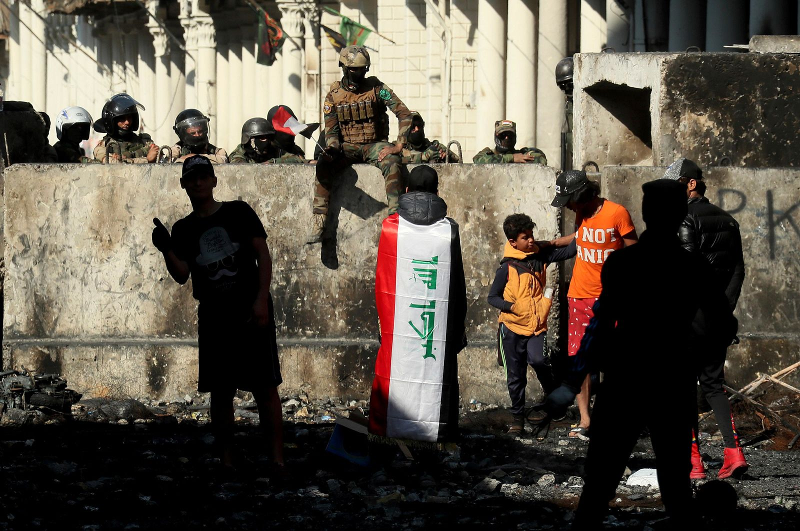 Iraqi security forces and anti-government protesters rest after both sides shake hands and converse in a rare moment of calm in hostilities called to allow time for rest after clashes in Baghdad, Iraq, Saturday, Nov. 30, 2019. (AP Photo/Hadi Mizban)