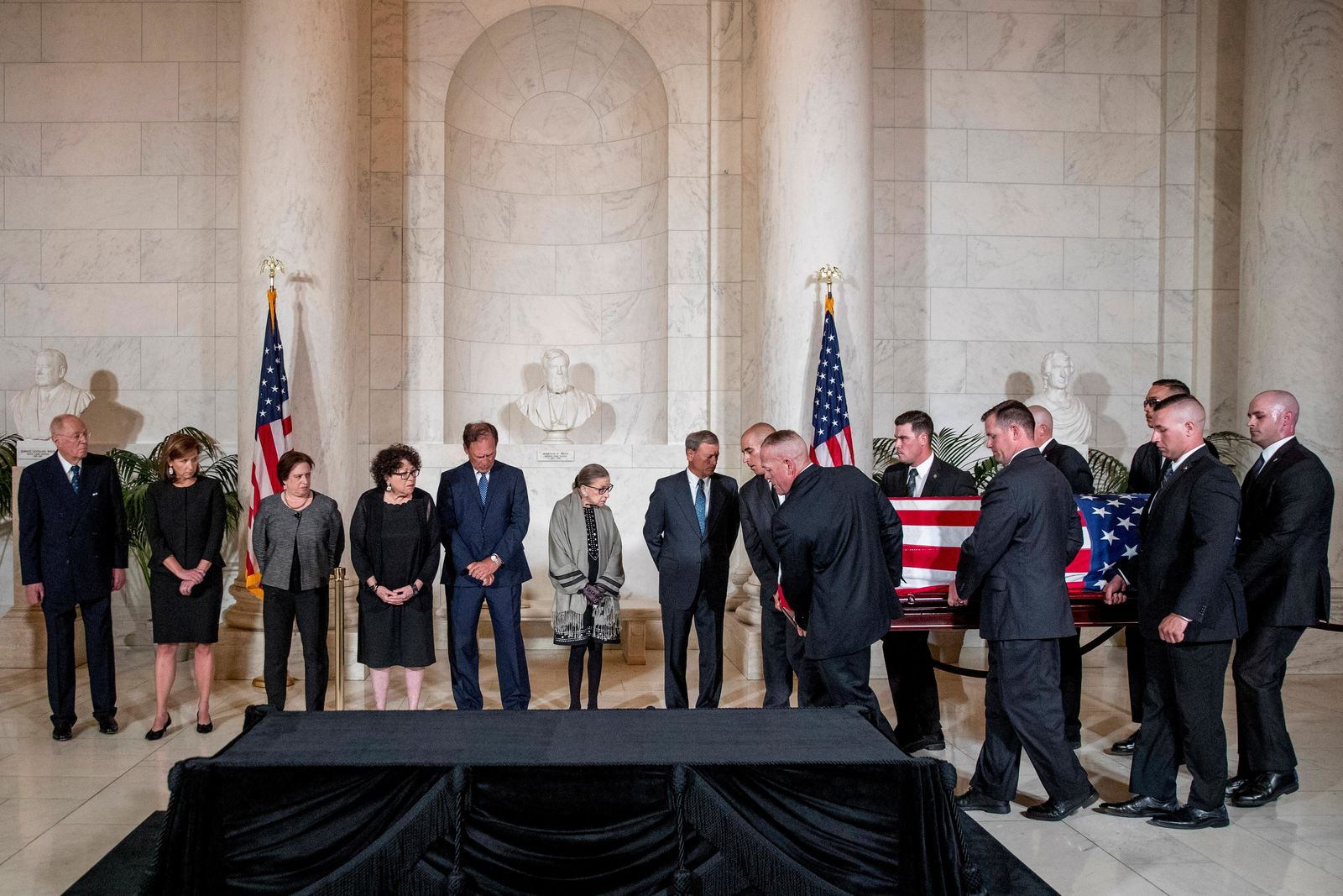 From left, retired Associate Justice Anthony Kennedy, Ashley Kavanaugh, the wife of Associate Justice Brett Kavanaugh, Associate Justice Elena Kagan, Associate Justice Sonia Sotomayor, Associate Justice Samuel Alito, Associate Justice Ruth Bader Ginsburg, and Chief Justice John Roberts watch as the casket of late Supreme Court Justice John Paul Stevens is carried into the Great Hall of the Supreme Court in Washington, Monday, July 22, 2019. (AP Photo/Andrew Harnik, pool)