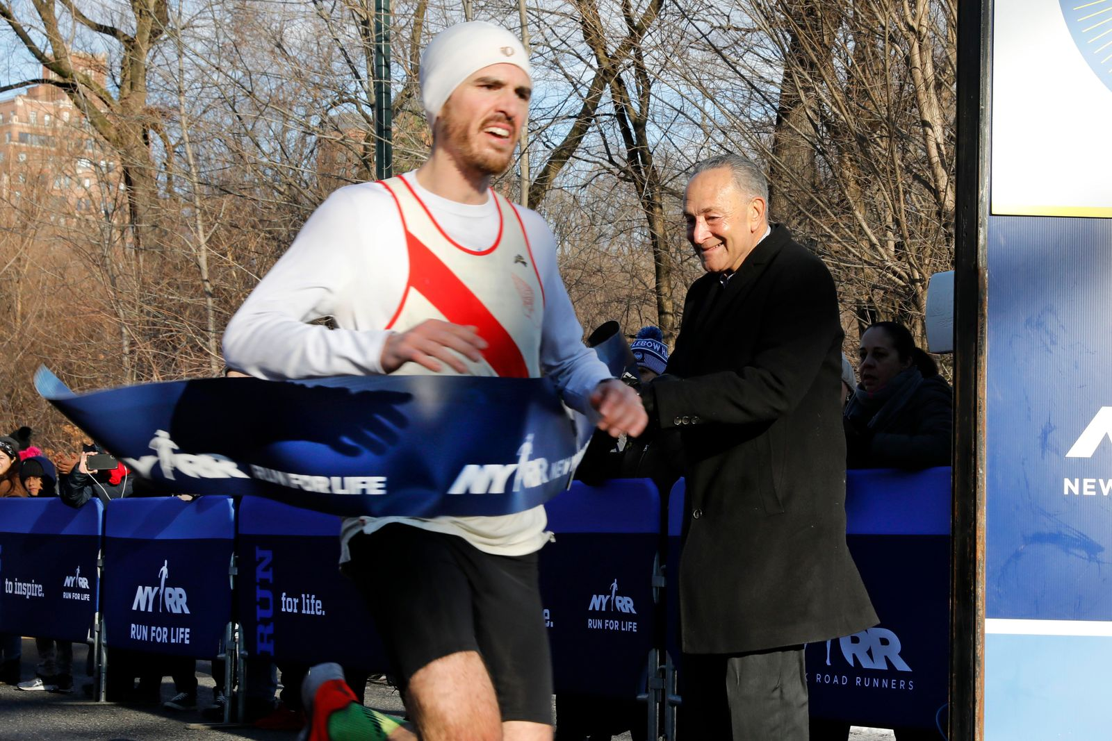 U.S. Senate Minority Leader Chuck Schumer, D-N.Y., holds the finish line tape, as Sean Swift, of Cranford, N.J., sets a course record to win the Fred Lebow Half Marathon, in New York's Central Park, Sunday, Jan. 19, 2020. (AP Photo/Richard Drew)