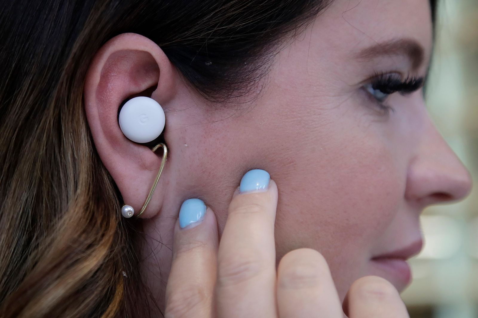 In this Tuesday, Sept. 24, 2019, photo  Isabelle Olsson, head of color & design for Nest, shows Pixel buds in her ear at Google in Mountain View, Calif. (AP Photo/Jeff Chiu)