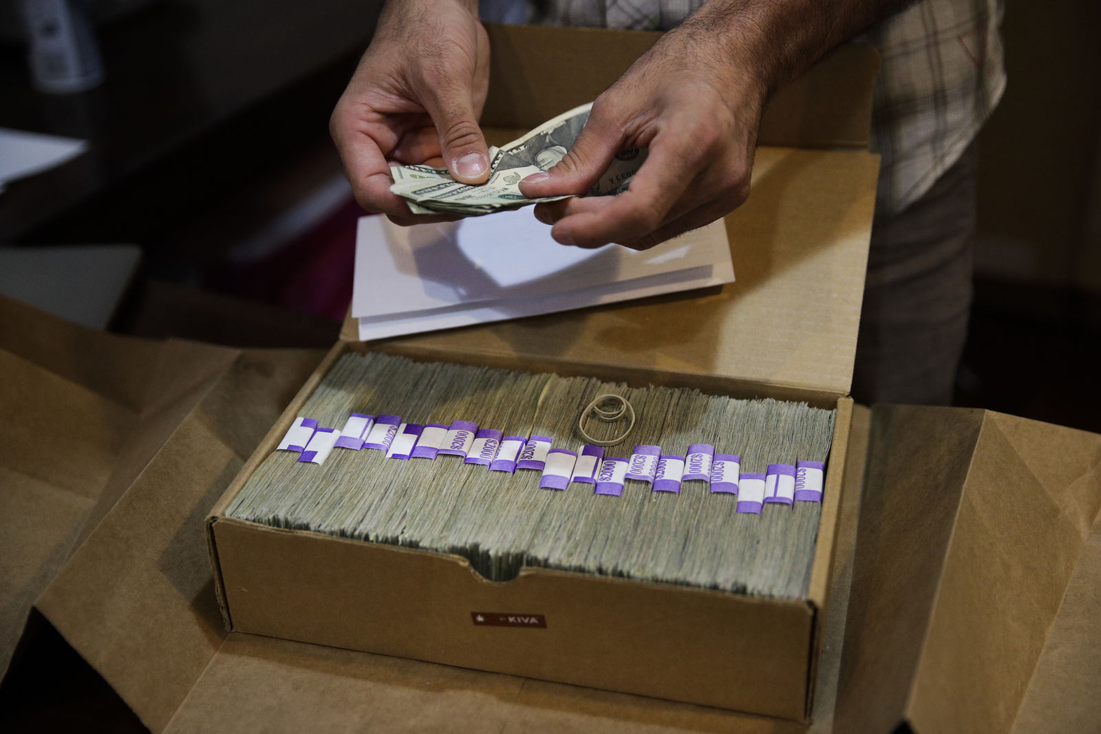 FILE - In this June 27, 2017 file photo, the proprietor of a medical marijuana dispensary prepares his monthly tax payment, over $40,000 in cash, at his Los Angeles store. Congress on Wednesday, Feb. 13, 2019, was urged to fully open the doors of the nation's banking system to the legal marijuana industry, a change that supporters say would reduce the risk of crime and resolve a litany of problems for pot companies from paying taxes to getting a loan. (AP Photo/Jae C. Hong, File)