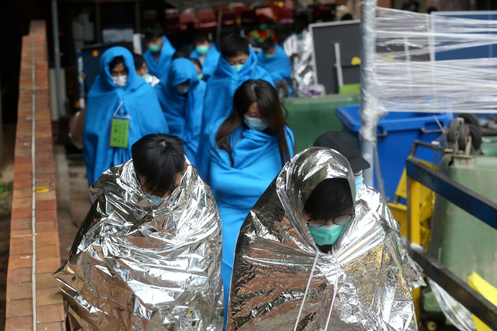 Injured protesters huddle under blankets as they walk at the Hong Kong Polytechnic University in Hong Kong, Tuesday, Nov. 19, 2019. (AP Photo/Achmad Ibrahim)