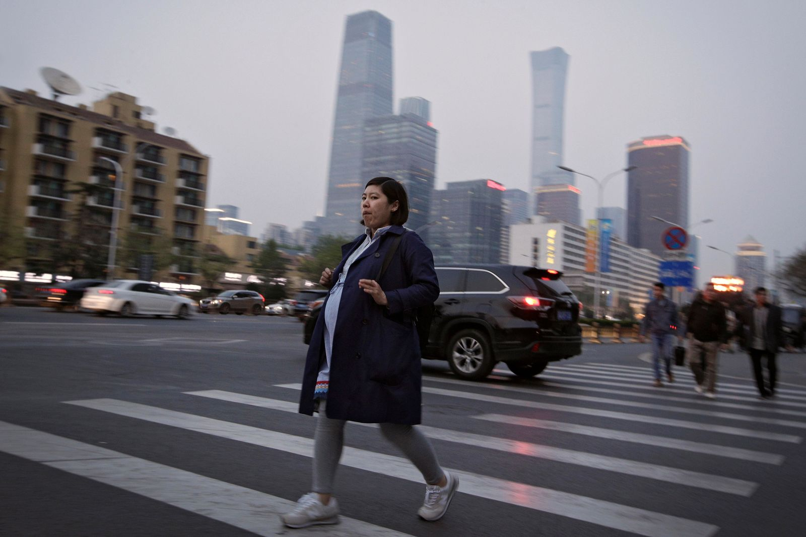 In this Wednesday, April 17, 2019, photo, a pregnant woman walks across a road near the Central Business District during the evening rush hour in Beijing. (AP Photo/Andy Wong)
