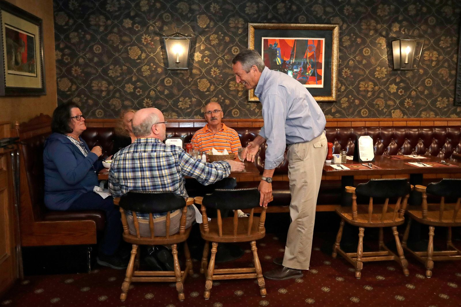 Republican presidential candidate, former South Carolina Gov. Mark Sanford, right, chats with{ }patrons at the Puritan Backroom restaurant, during a campaign stop, Thursday, Sept. 19, 2019, in Manchester, N.H. (AP Photo/Elise Amendola)