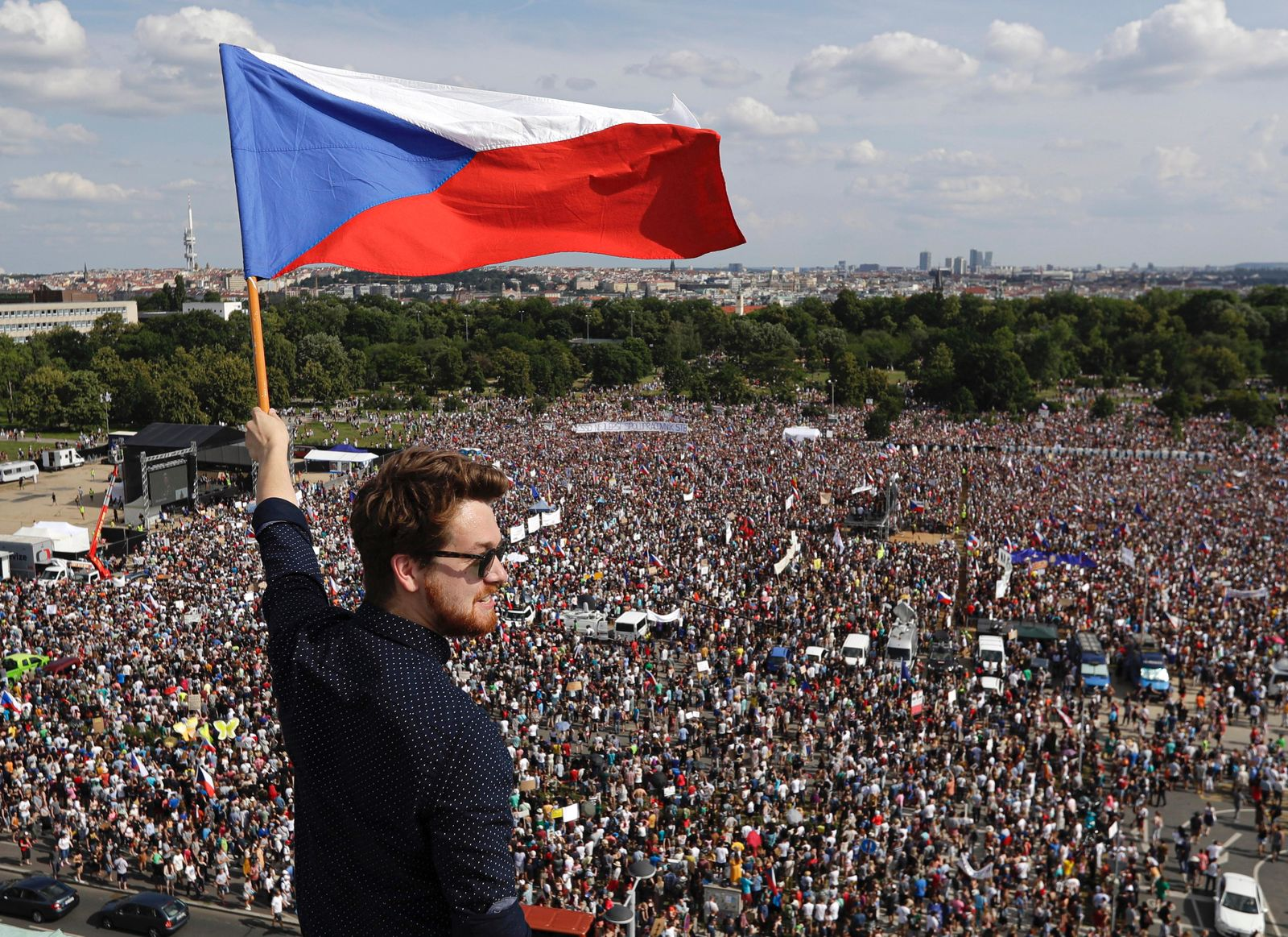A man waves the Czech flag as people protest in Prague, Czech Republic, Sunday, June 23, 2019. Protesters are on calling on Czech Prime Minister Andrej Babis to step down over fraud allegations and subsidies paid to his former companies. (AP Photo/Petr David Josek)