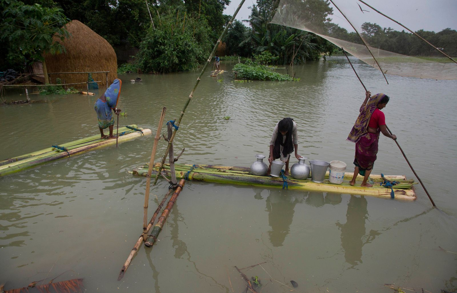 Indian flood affected women row makeshift banana rafts to collect drinking water in Pabhokathi village, east of Gauhati, Assam, India, Monday, July 15, 2019. (AP Photo/Anupam Nath)