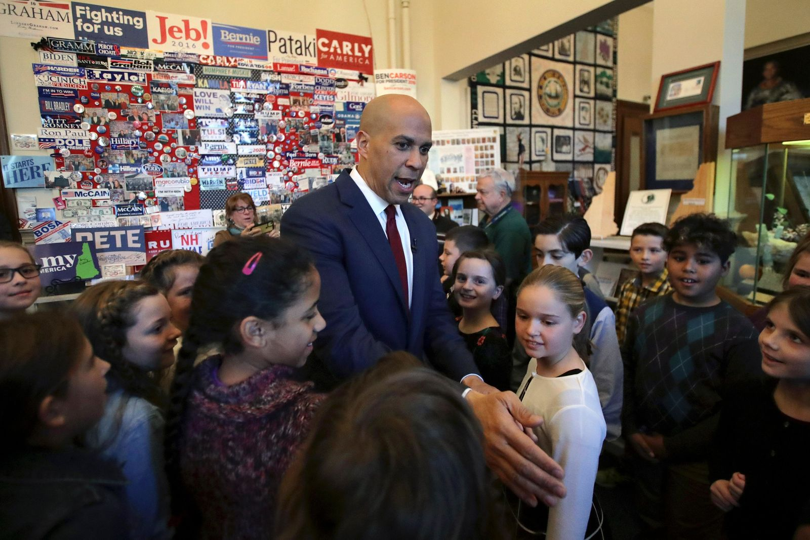 Democratic presidential candidate Sen. Cory Booker, D-N.J., passes by students from Bow Elementary School who were on a field trip to the State House as he departs after filing to have his name listed on the New Hampshire primary ballot, Friday, Nov. 15, 2019, in Concord, N.H. (AP Photo/Charles Krupa)