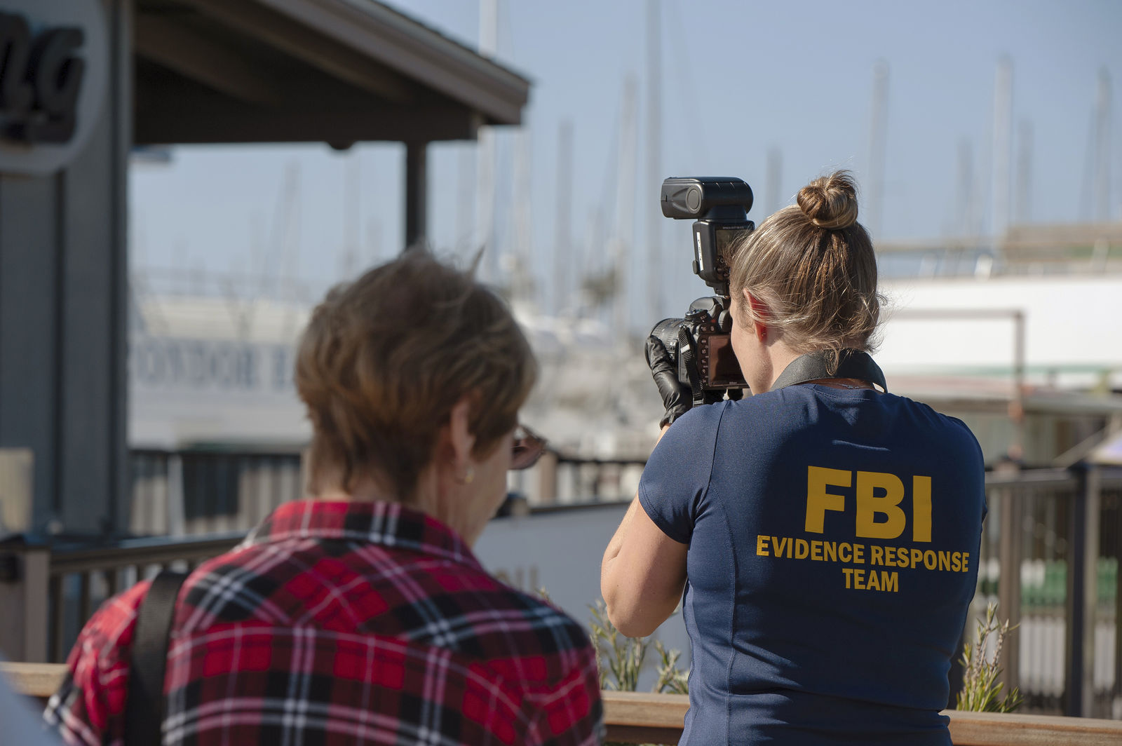 An FBI photographer takes evidence pictures as authorities search the Truth Aquatics' offices, the California company that owned the scuba diving boat that caught fire and killed dozens of people last week, on the Santa Barbara Harbor in Santa Barbara, Calif., Sunday, Sept. 8, 2019. (AP Photo/ Christian Monterrosa)