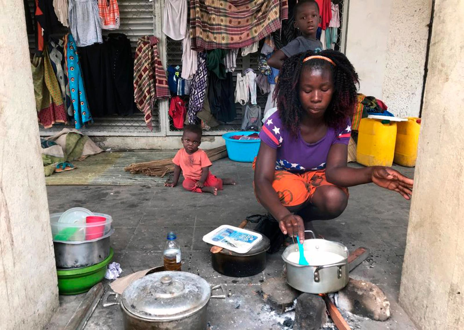 Marta Ben prepares food on a sidewalk after her home was destroyed in Beira, Mozambique, Friday March 22, 2019. . (AP Photo/Cara Anna)