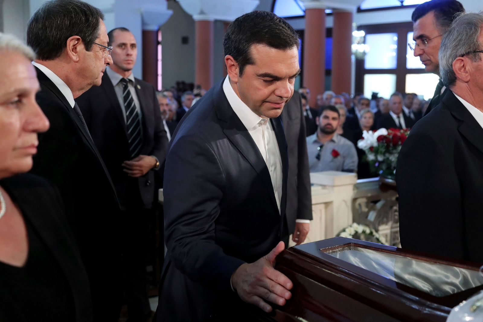 Greece's Prime minister Alexis Tsipras touches the coffin of the former Cyprus' President Dimitris Christofias during his state funeral at the Orthodox Christian Church of the Lord's Wisdom in capital Nicosia, Cyprus, Tuesday, June 25, 2019. European communist and left-wing party heads and leaders from ethnically split Cyprus' breakaway Turkish Cypriot community were among those attending a funeral service for the country's former president Christofias. (AP Photo/Petros Karadjias)