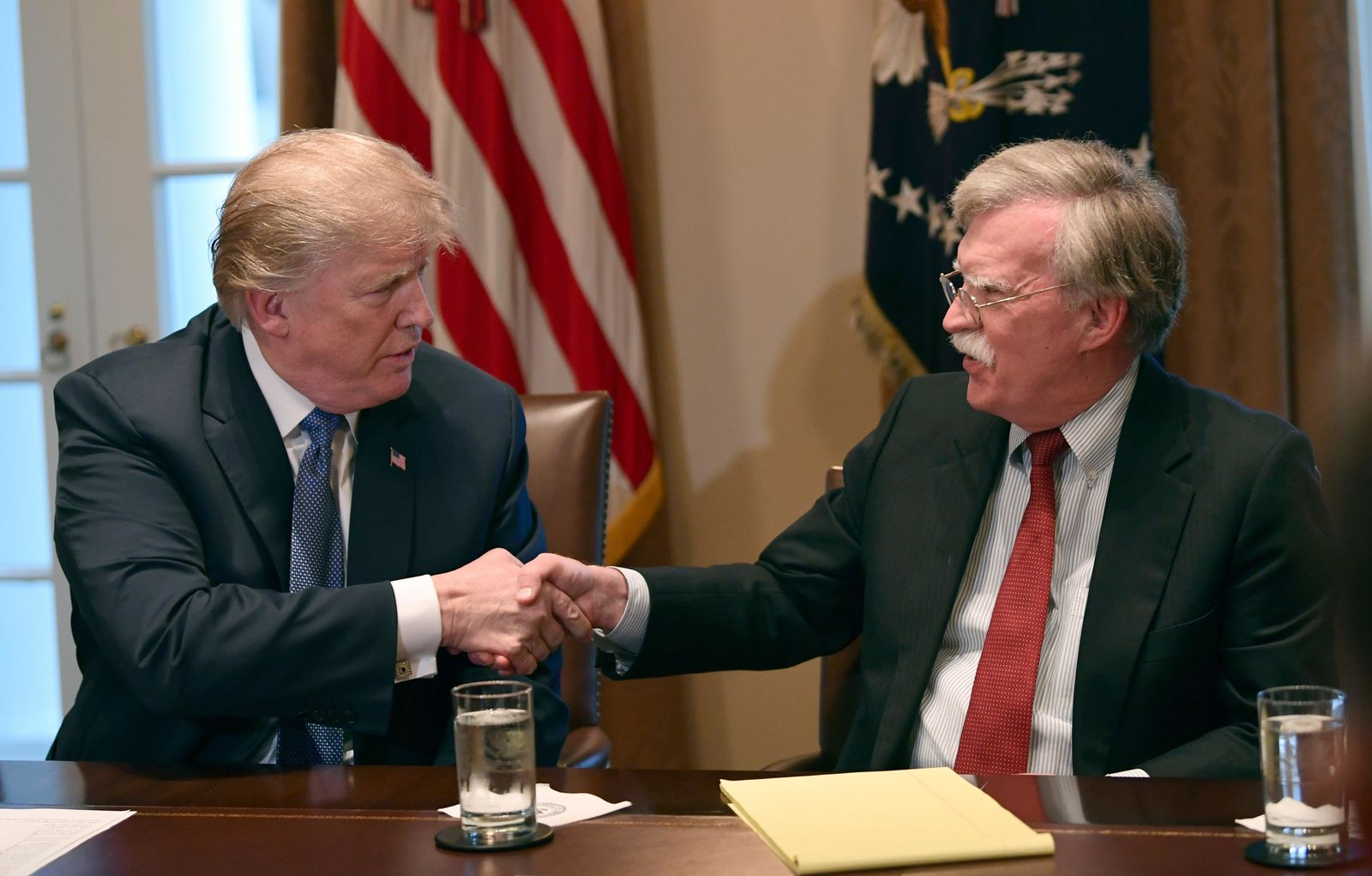 FILE - In this April 9, 2018 file photo, President Donald Trump, left, shakes hands with national security adviser John Bolton in the Cabinet Room of the White House in Washington at the start of a meeting with military leaders. (AP Photo/Susan Walsh)