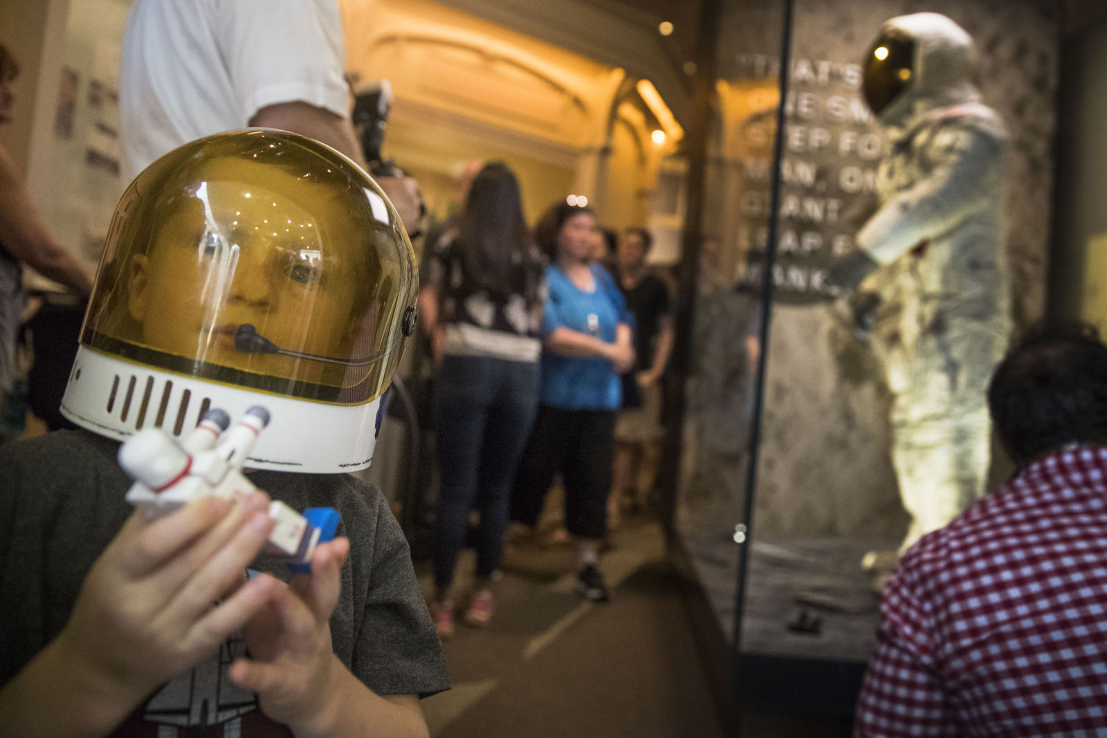 Jack Heely, 5, of Alexandria, Va., wears a toy space helmet as he arrives as one of the first visitors to view Neil Armstrong's Apollo 11 spacesuit, background, after it is unveiled at the Smithsonian's National Air and Space Museum on the National Mall in Washington, Tuesday, July 16, 2019. (AP Photo/Andrew Harnik)