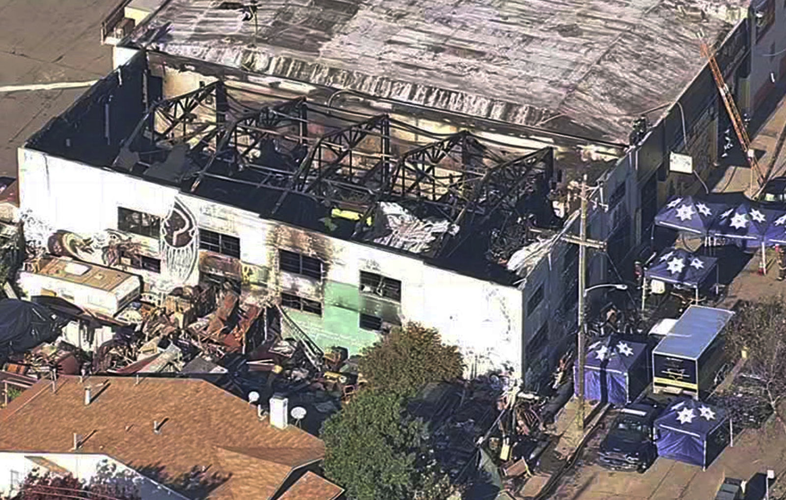 FILE - This Dec. 3, 2016, file image from video provided by KGO-TV shows the Ghost Ship Warehouse after a fire swept through the building in Oakland, Calif. A jury has decided the fate of two men charged with involuntary manslaughter after prosecutors say they turned a San Francisco Bay Area warehouse into a cluttered maze that trapped 36 partygoers during a fast-moving fire. The verdicts for Derick Almena and Max Harris will be announced Thursday, Sept. 5, 2019, after a three-month trial that drew family and friends of the victims to a packed courtroom, said Almena's attorney, Brian Getz. They face up to 39 years in prison if convicted. (KGO-TV via AP, File)
