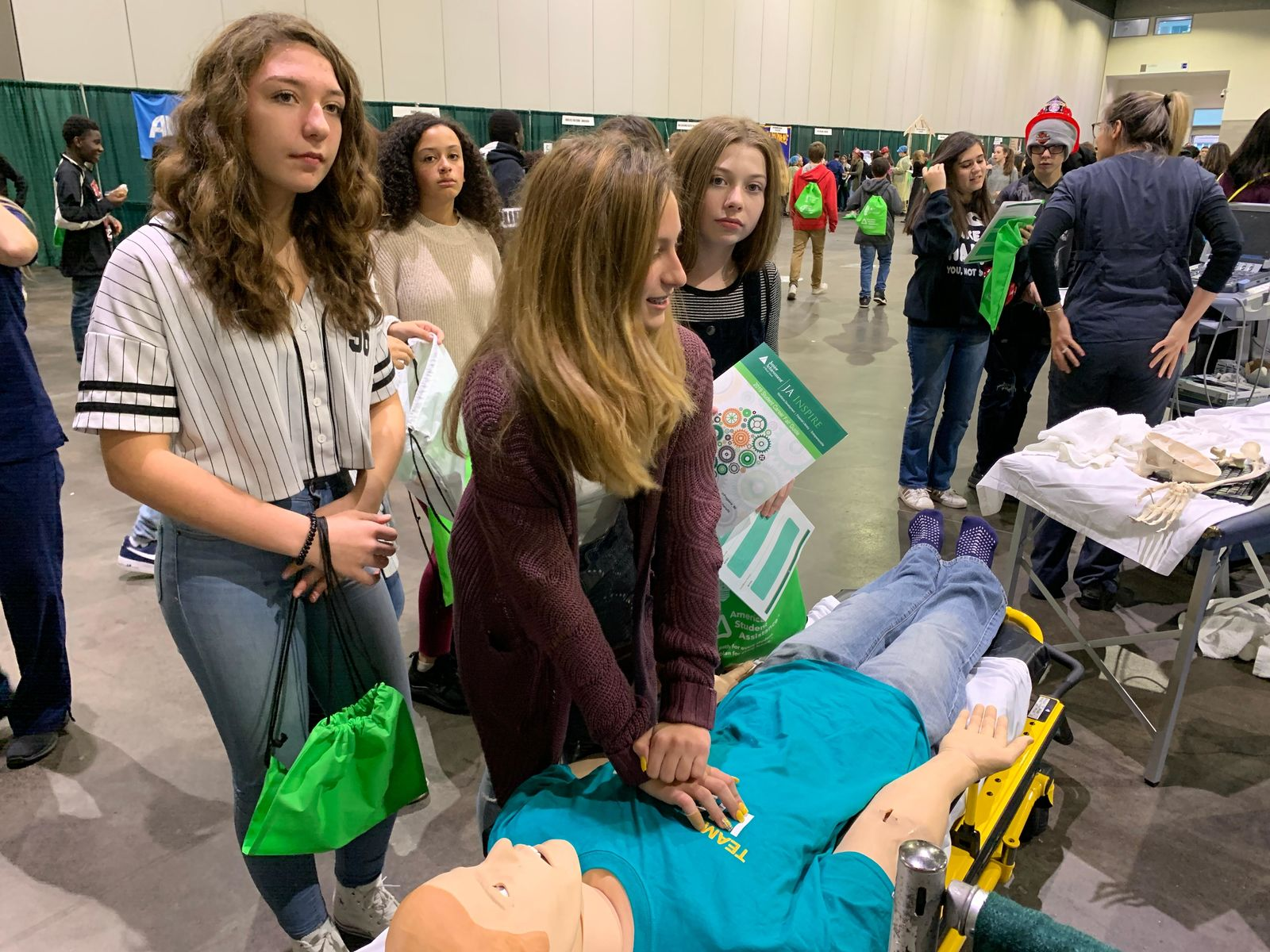Sophia Schmitt, a student at Warwick Vets Middle School, stopped at the Lifespan exhibit to practice CPR. (WJAR)