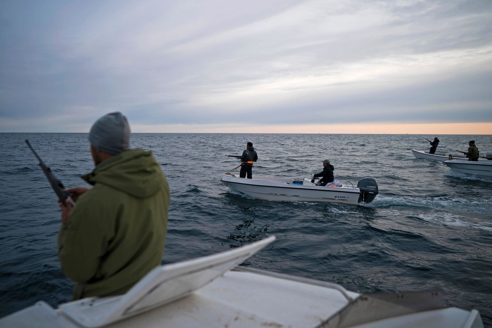 In this Aug. 16, 2019, photo, Mugu Utuaq, left, reloads his rifle as he rides with other boats hunting whales near Kulusuk, Greenland. Summer in 2019 is hitting the island hard with record-shattering heat and extreme melt.{ } (AP Photo/Felipe Dana)